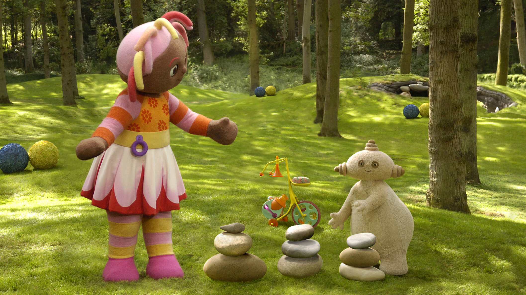 A girl with a colourful dress and hair is standing in a park beside stacked rocks and a uniquely shaped beige character.