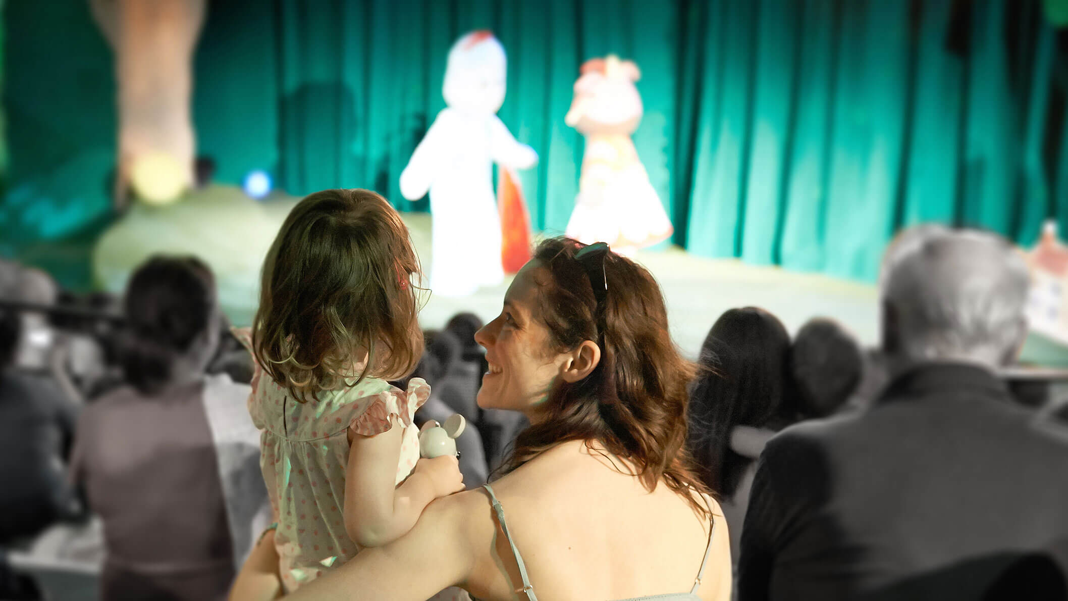 A mother and her young daughter sitting inside a theatre, with a stage in the background and people in their seats.