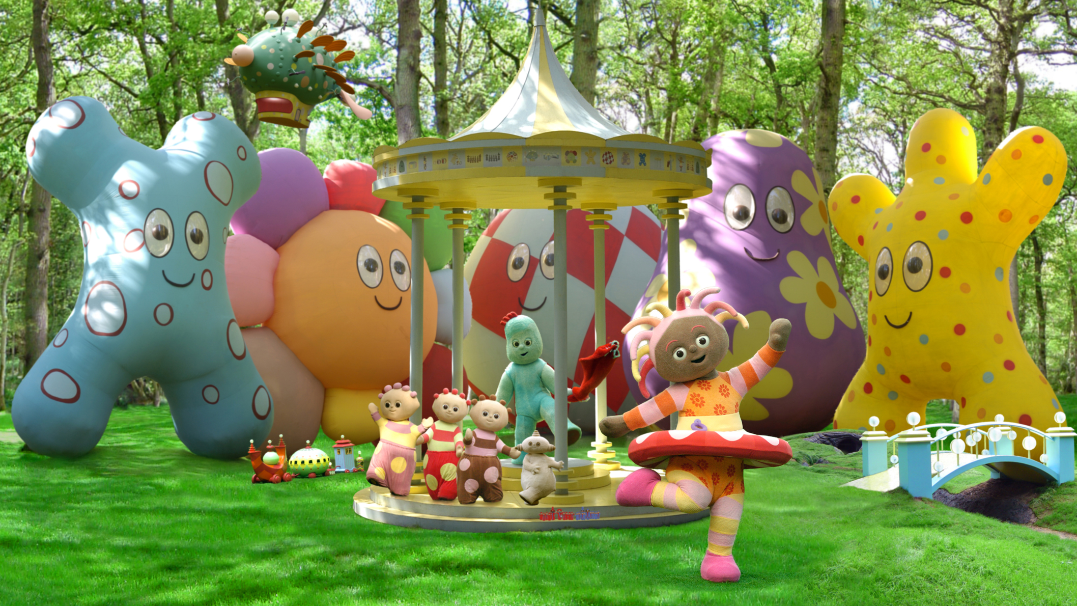 Six character in varios shapes and sizes playing in the middle of a park. Behind them are tall trees and huge, colourful balloons.