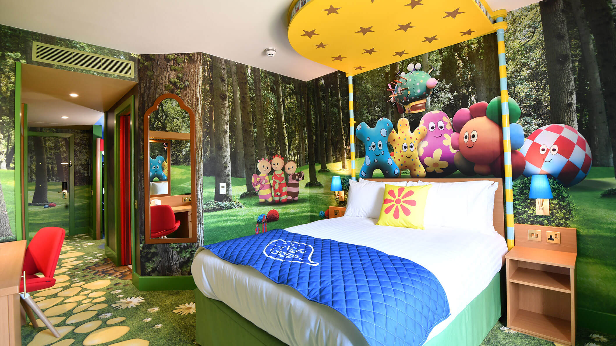 A colourful kids bedroom with wallpaper of a forest and cute characters.