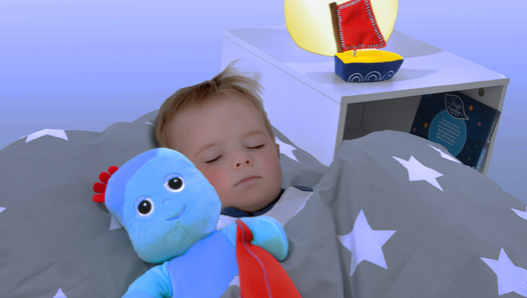 A toddler sleeping in his bed beside a blue toy holding a red blanket. There is a side table with a lamp and a toy on it.