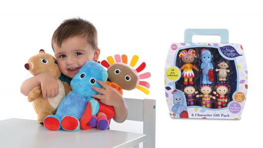 A toddler sitting at a table is smiling and hugging three soft toys. Behind the toddler is a white background and a toy packaging on the right side.
