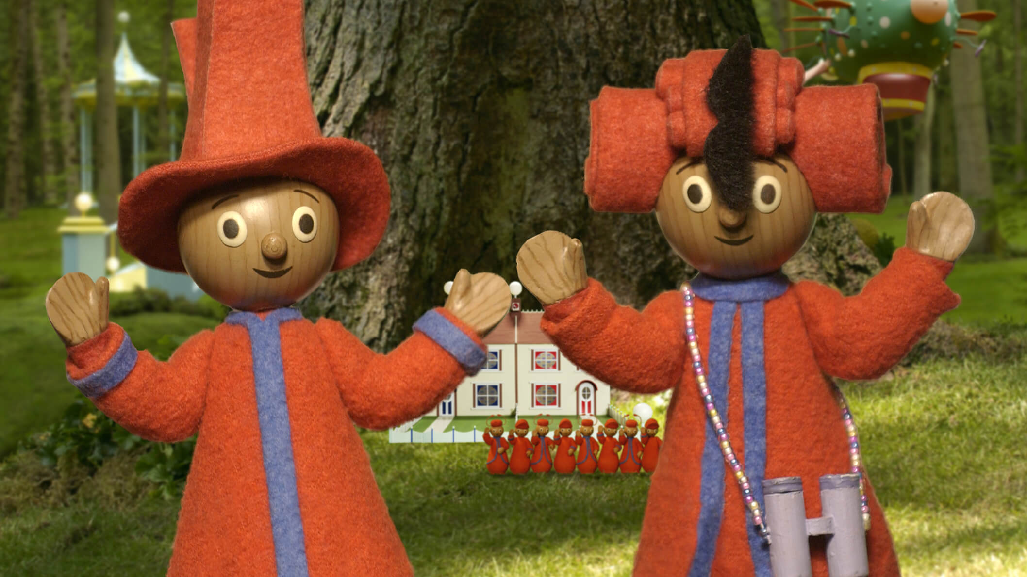 Two wooden characters, wearing red outfits and hats, holding their hands up in front of a big tree.