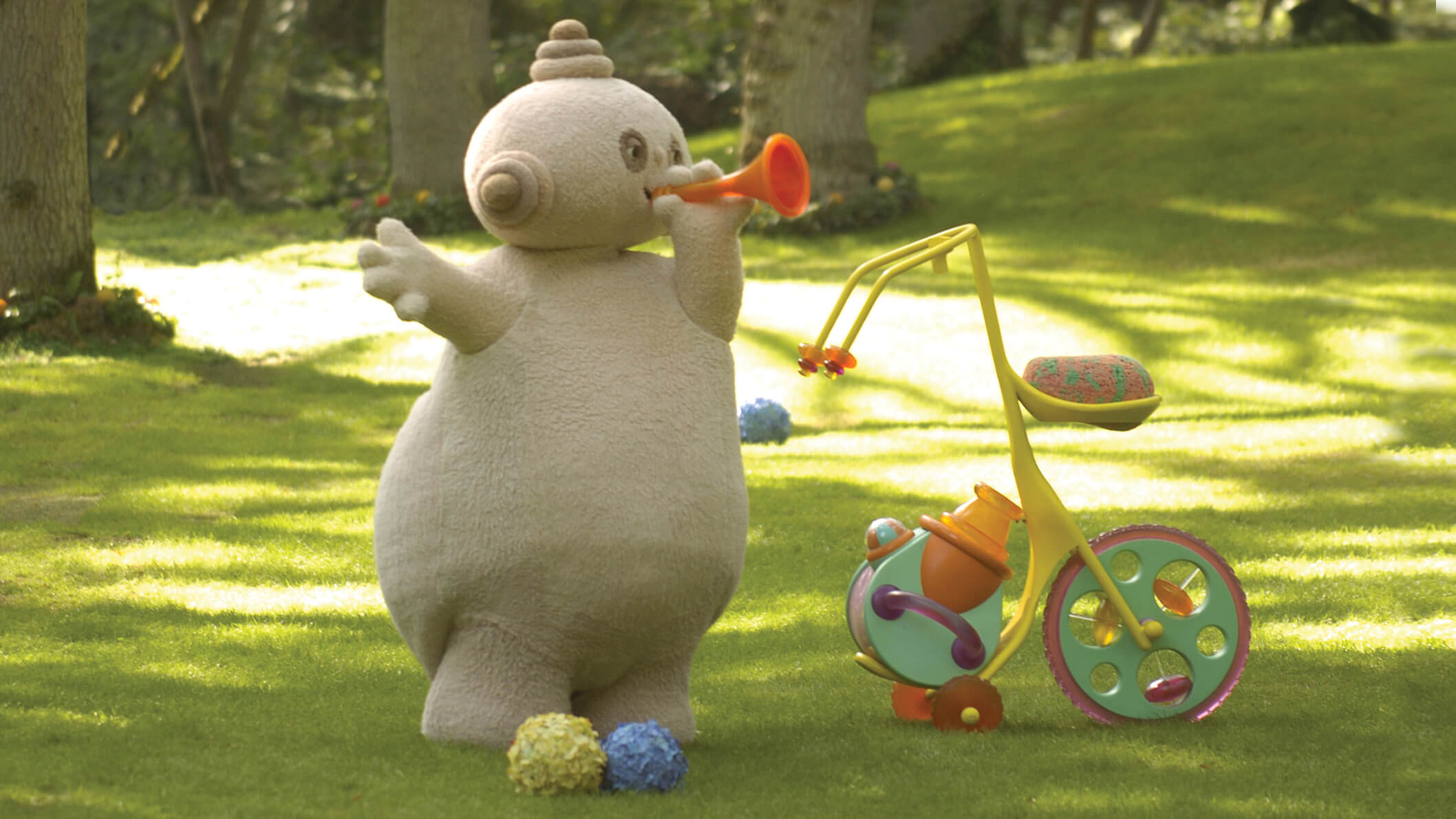 A round, beige character standing in a park, beside a tricycle and blowing through an orange horn.