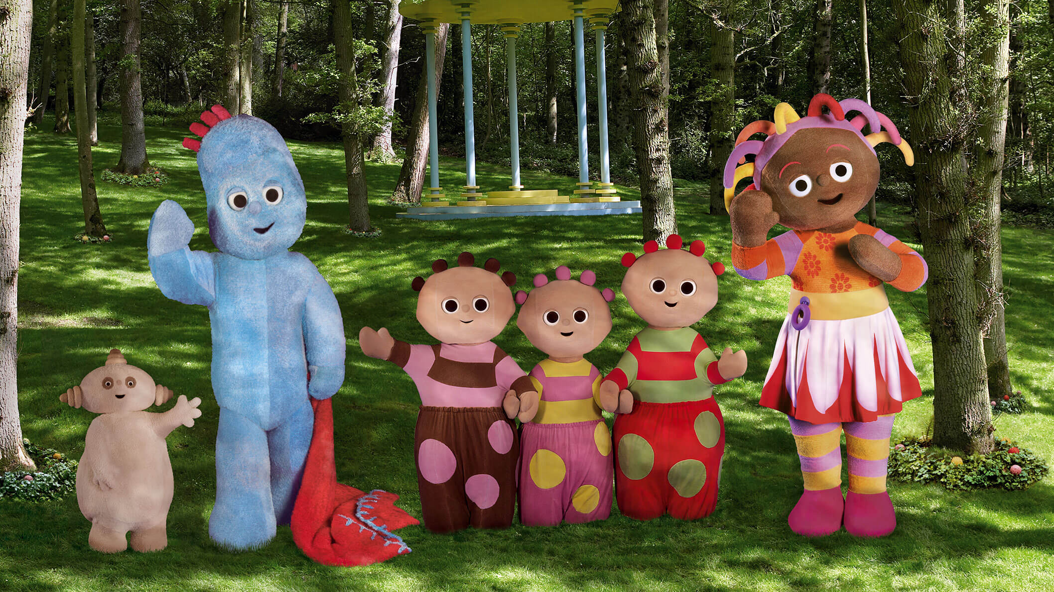 Six characters in various shapes and sizes standing in the middle of a park and waving.