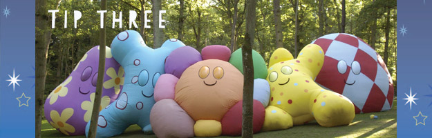 Five massive pillows, in various shapes and colours, leaning against each other in a green park.