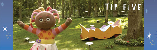 A brown, female character with colourful, stringy hair is holding her arms wide open in a park. There is a yellow bed on the grass in the background.