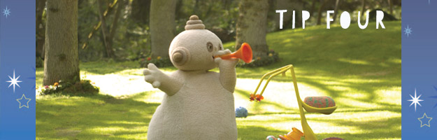A beige character, holding an orange horn close to it's mouth, is standing in the middle of a green park.