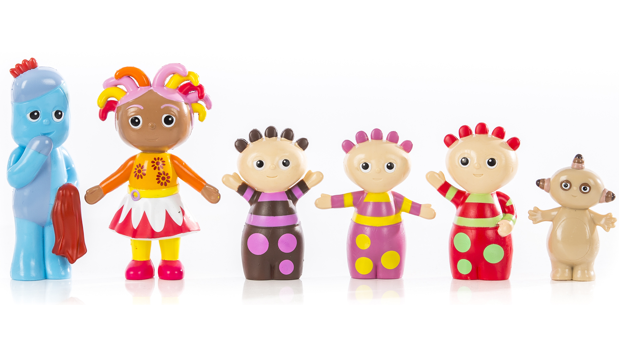 Six colourful toys in various shapes and colours, lined up next to each other in front of a white wall.