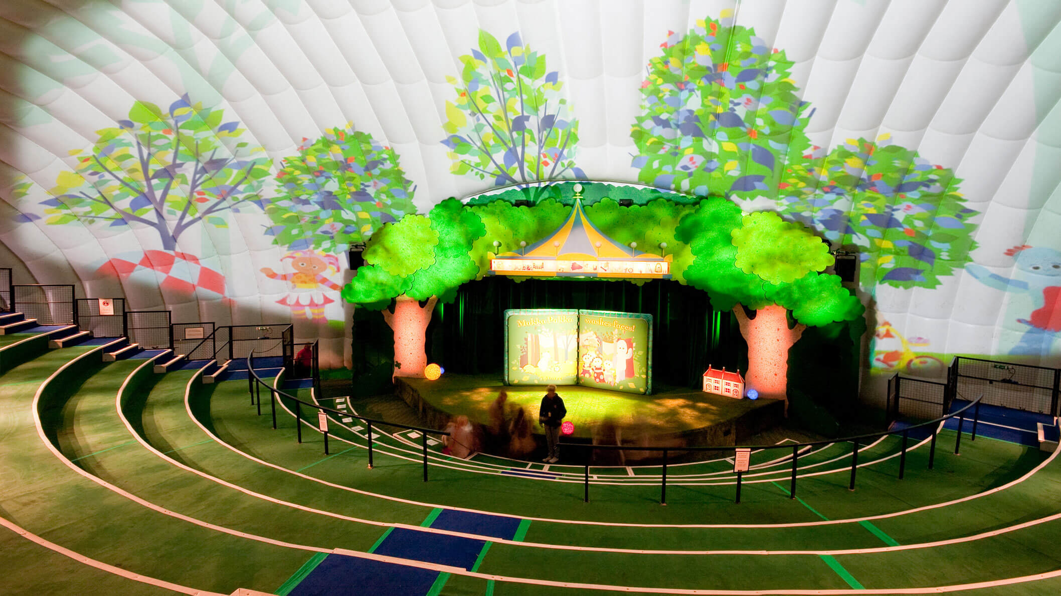A stage inside a white tent with two trees on each side. There is a projection of colourful trees and two characters on the tent walls.