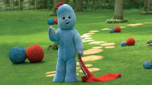 A blue character with a red patch of hair, holding a red blanket and standing in a green park with a cobble stone path in the background.