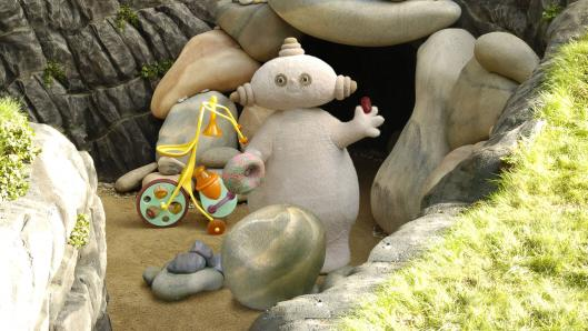 A beige character, with an oval shaped head, standing in front of a cave entrance.