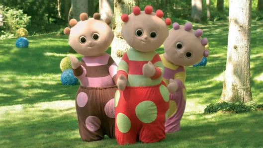 Three characters, in colourful, polka dot costumes, standing beside each other in a green park.