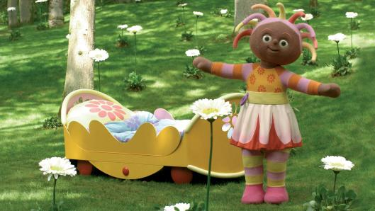 A brown, female character in a colourful dress, standing in a park with a yellow bed behind her. She is smiling and has her arms spread open.