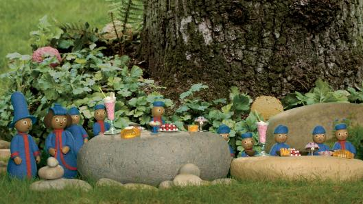 Miniature characters, wearing the same blue uniforms, sitting on large rocks in front of a tall tree.